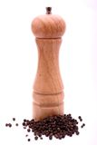 Pepper mill on white. A pepper mill with black peppercorns against a white background Stock Images