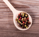 Pepper mixture. On spoon over wooden background Stock Images