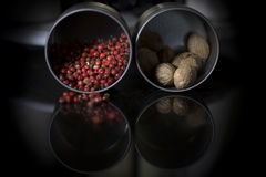 Pepper and nutmeg. Colors. Red peppercorns and nutmeg in metallic boxes. Black granit table. Reflexion Stock Images