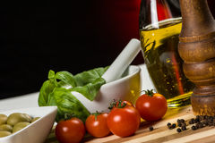 Pepper, oil , olives and tomatoes. A bottle of olive oil togheter with fresh cherry tomatoes, some basil, green olives and a pepper mill Royalty Free Stock Image