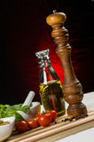 Pepper, oil , olives and tomatoes. A bottle of olive oil togheter with fresh cherry tomatoes, some basil, green olives and a pepper mill Stock Photo