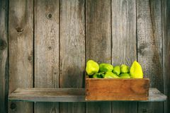 Pepper in an old box on a wooden shelf. Stock Photos
