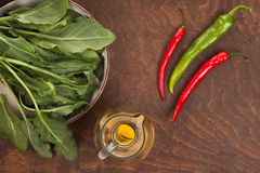 Pepper, olive oil and green leaves. On a dark wood table Royalty Free Stock Photo