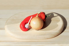 Pepper, onion, garlic and cutting Board Royalty Free Stock Photography