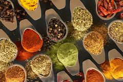 Various spices for dishes on a black background, camera from above stock images