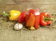 Pepper. Pickled peppers are in a glass jar. Fresh red and yellow sweet pepper is on a table stock photography