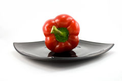 Pepper on plate. Red pepper on black plate isolated on white Royalty Free Stock Photos