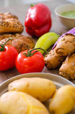 Pepper, potato, kaiser bun and baguette on wood table. Vegetarian bio food concept. Royalty Free Stock Photo