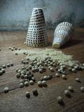 Pepper powder and peppercorns. Pepper powder spill out of the shells and scattered peppercorns on a wooden board Royalty Free Stock Images