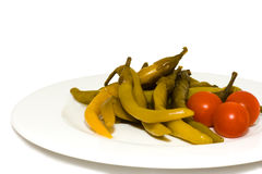 Pepper and red tomatoes on the white plate. Close-up Stock Photography