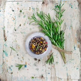 Pepper and rosemary on wooden board Stock Image