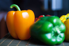 Pepper in a row. Orange and green sweet pepper in a row on a wooden plate Royalty Free Stock Photo