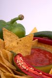 Pepper and salsa. Nachos, salsadip and ingredients against a white background with plenty of copyspace Royalty Free Stock Photos