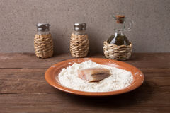 Pepper, salt, olive oil and one piece of fresh fish with flour o Royalty Free Stock Photos