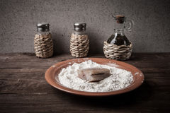 Pepper, salt, olive oil and one piece of fresh fish with flour o Stock Image