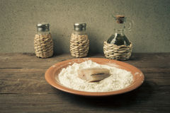Pepper, salt, olive oil and one piece of fresh fish with flour o Royalty Free Stock Image