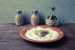 Pepper, salt, olive oil and one piece of fresh fish with flour o Royalty Free Stock Photo