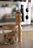 Pepper shaker and ginger. Pepper shaker and jar full with ginger roots on the kitchen board and a microwave oven on the background Royalty Free Stock Images
