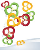 Pepper slice. An illustration of slices of red yellow and green peppers tumbling in to water on a white background Royalty Free Stock Images