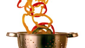 Pepper slices falling into colander stock video footage