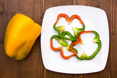 Pepper slices on plate on wood from above Stock Photo
