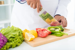 Pepper slicing. Cropped image of a professional cook slicing pepper on the cutting board Stock Photography