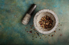 Pepper spice mix in a mortar. On a green background, selective focus Royalty Free Stock Photography