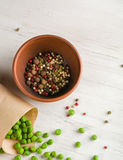 Pepper and spices in a bowl. Green peas in a paper bag. Royalty Free Stock Image