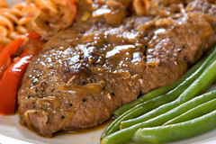 Pepper Steak. Lamb steak close up with green beans and peppers. focus on the steak Stock Photography