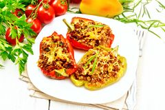 Pepper stuffed with meat and couscous in plate on light board royalty free stock photography