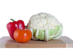 Pepper, tomato and cauloflower. Organic vegetables - bell pepper, tomato and cauliflower on a cutting board Stock Photos