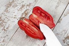 Pepper tomato cut with knife on white wood royalty free stock photos