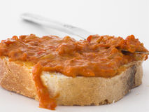 Pepper-tomato mash spread. Slice of bread with pepper-tomato mash spread on top with knife in background Stock Images