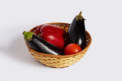 Pepper, tomato and two black eggplants lie in the wattled plate Royalty Free Stock Images