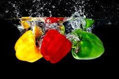 Pepper in Water. Pepper Red Yellow Green fall into Water, Black background stock photos