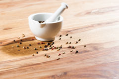 Pepper on wood tabel. Pepper on wood table with white mortar Royalty Free Stock Image