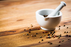 Pepper on wood tabel. Pepper on wood table with white mortar Stock Image