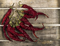 Pepper on wooden background. Red peppers attached to a string on wooden background Royalty Free Stock Images