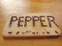 Pepper written on cutting board with pepper Royalty Free Stock Images