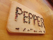 Pepper written on cutting board with pepper Stock Photos