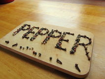 Pepper written on cutting board with pepper. Pepper word written on cutting board with pepper royalty free stock image