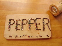 Pepper written on cutting board while peppermill lies next to it. Pepper word written on cutting board with pepper. Peppermill lies next to it Royalty Free Stock Photography