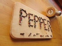 Pepper written on cutting board while peppermill lies next to it Royalty Free Stock Photo