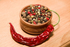 Peppercorn and chilli on a wooden surface. A mixture of grains of pepper and chili peppers on a wooden surface Royalty Free Stock Photography