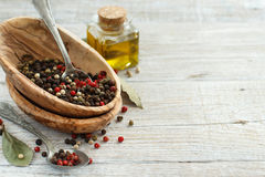 Peppercorn mix in a bowl, bay leaves  and olive oil Stock Photos