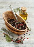 Peppercorn mix in a bowl, bay leaves  and olive oil Royalty Free Stock Photography