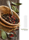 Peppercorn mix in a bowl and bay leaves Stock Photo