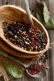 Peppercorn mix in a bowl and bay leaves Stock Photos