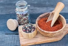 Peppercorn mix and  crushed paprika in a wooden bowl and glass jar on an old dark wooden table. Peppercorn mix and crushed paprika in a wooden bowl and glass Royalty Free Stock Photo