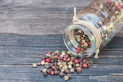 Peppercorn mix in a glass jar on an old dark wooden table. Red peppers cut and crushed in wooden bowl on wooden background. With copy space Royalty Free Stock Photography